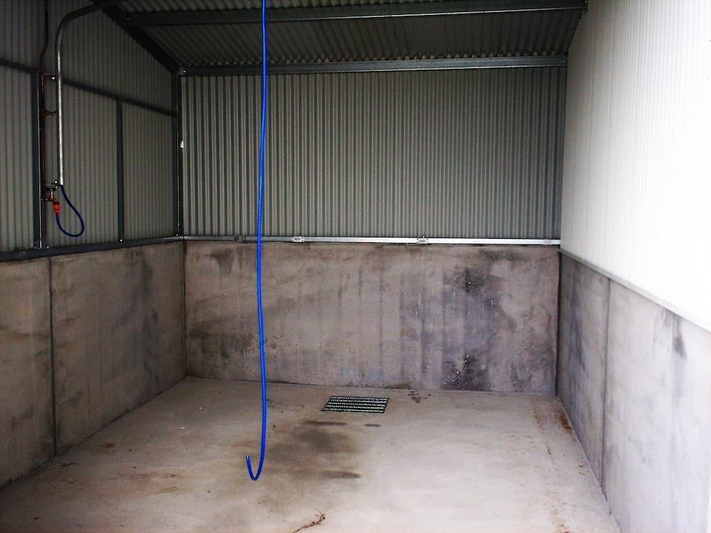 Half height concrete and colorbond wall enclosed washbay External enclosed washbay half height precast concrete panels colorbond wall cladding central pit drain
