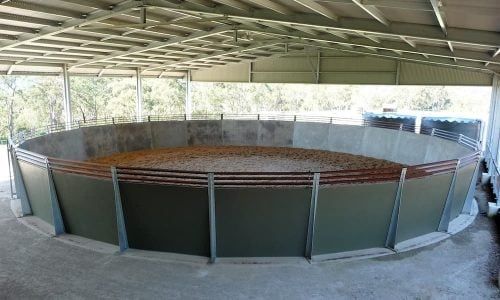 Precast concrete round yard with angled segmented walls and timber rails