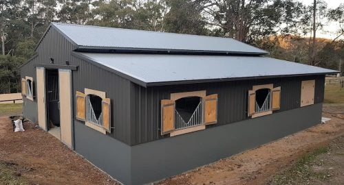 Stable barn half height precast concrete and colorbond walls breezeway vent shutters and sliding entry doors shadow clad
