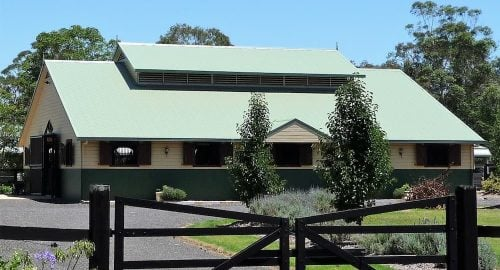 Stable breezeway barn half height precast concrete and weatherboard walls louvre vents colorbond roof swinging entry doors hardwood shutters
