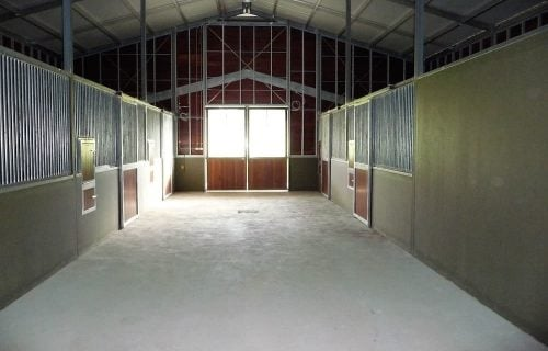 Breezeway barn half height precast concrete and grill walls rotating feed bins hay rack hardwood timber and glass entry doors