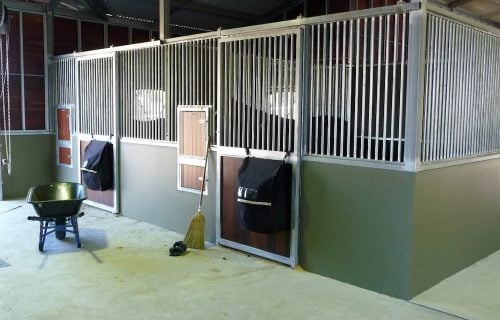 Breezeway barn half height precast concrete and grill walls rotating feed bins hay rack hardwood timber and grill sliding stable doors
