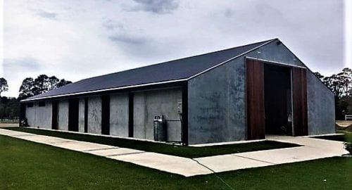Modern stable breezeway barn patterned precast concrete walls box gutter full height hardwood timber sliding doors