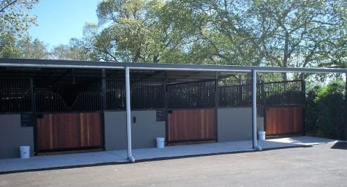 Open front stable with verandah precast concrete and powder-coated grill walls swinging stable doors
