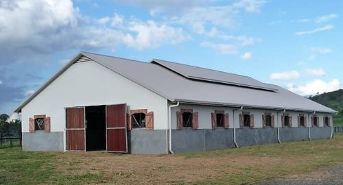Stable barn half height precast concrete and colorbond walls breezeway vent hardwood shutters and swinging entry doors