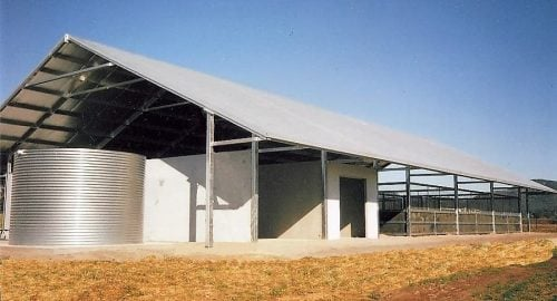Open stable high pitch roof precast concrete and steel and rubber walls covered yards