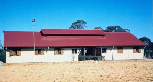 Stable cross breezeway barn precast concrete walls hardwood timber shutters vented roof