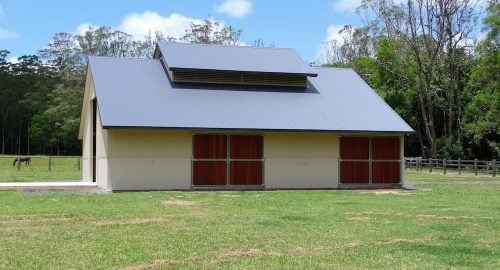 Stable high pitch colorbond roof louvre vents half height precast concrete and colorbond walls swinging steel frame hardwood lined entry doors